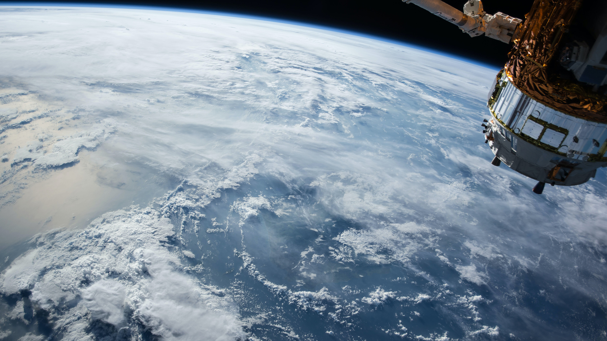 Earth with clouded skies and a satellite viewed from space.